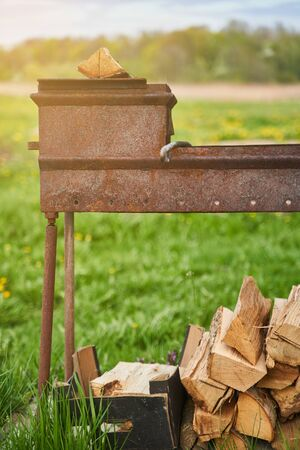 Barbecue for cooking meat on fire. With prepared logs for lighting a fire.