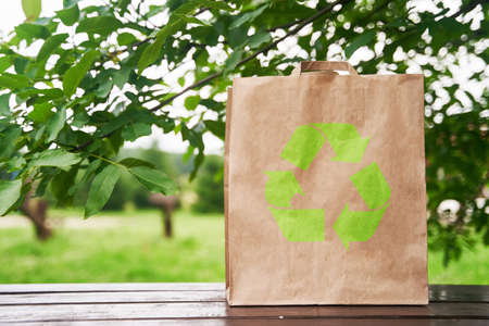 Empty paper bag stands on a wooden table against the background of green leaves. Shopping concept. High-quality photo.