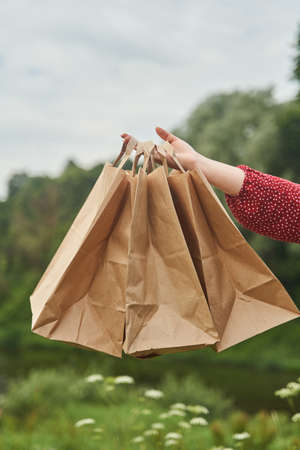 A young girl holds blank paper bags in her hand. Shopping concept. High-quality photo