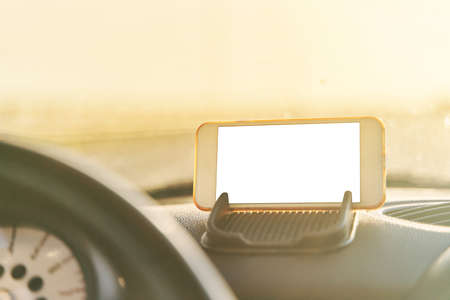 The map on the phone in the background of the dashboard.