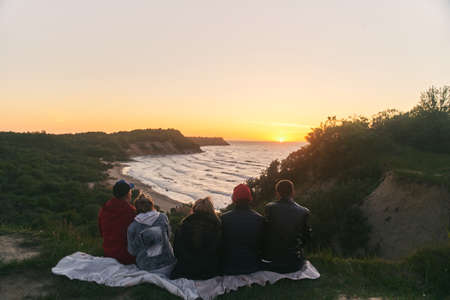 A group of friends watching the sunset at sea. View from the back 写真素材