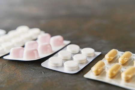 Pills capsules medicine health on dark background, top view 写真素材