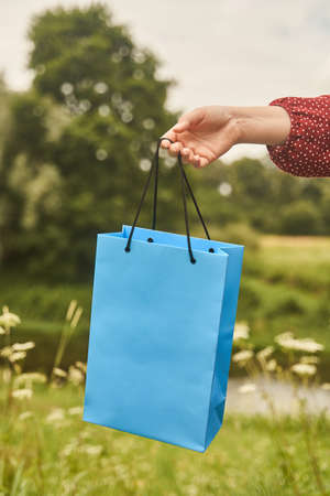 A young girl holds a blank paper bag in her hand. Shopping concept 写真素材