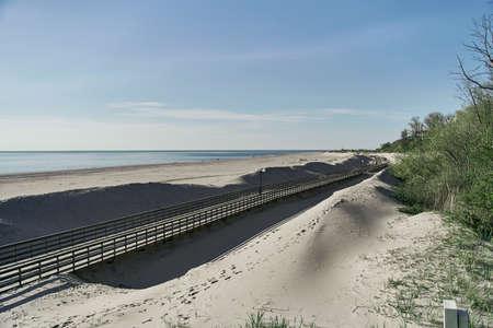 Wooden Boardwalk on Yantarniy Beach. Beach with a blue flag. Kaliningrad region