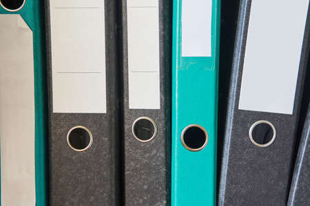 Colored folders for office files and paper on a shelf. Background image