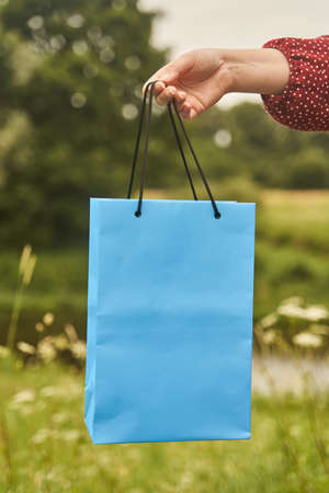 A young girl holds blank paper bags in her hand. Shopping concept
