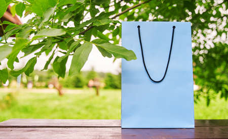 Blank paper bag stands on a wooden table against the background of green leaves. Shopping concept. Copy space. 写真素材