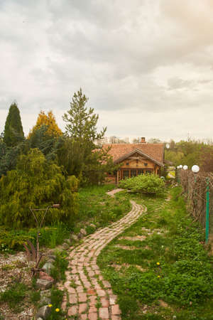 Brick winding path to a wooden house