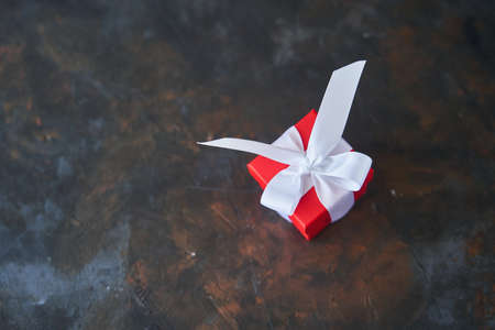 Small red gift box with white bow on dark background