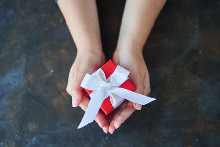 Woman holding small red present box in hands.