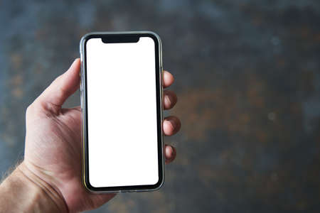 A young man holds in his hand a modern smartphone with a white screen on a dark background. Mockup