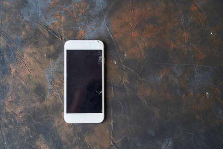 White phone with a broken screen on dark background