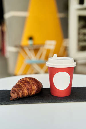 Red cup with coffee and a croissant on a table in a cafe.