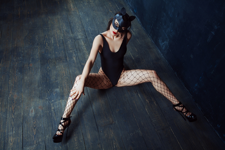 Beautiful slender girl in a black slip, leather cat mask, in black pantyhose, in black high hills sitting on the floor with legs apart. BDSM concept