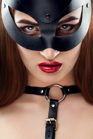 Vertical portrait of female model. Closeup of girl face with black mask, soft skin, color red lipstick, swaths on the neck. BDSM concept