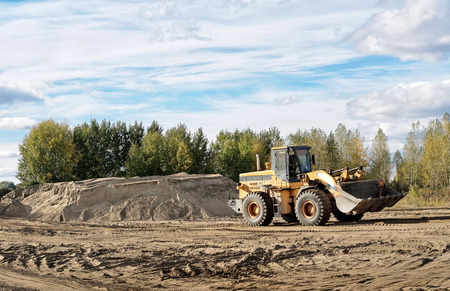 construction vehicle: The work of the tractor in a sand pit in the summer in Sunny weather Editorial