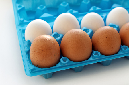insulated drink container: A set of yellow and white eggs in blue plastic container - side view Stock Photo