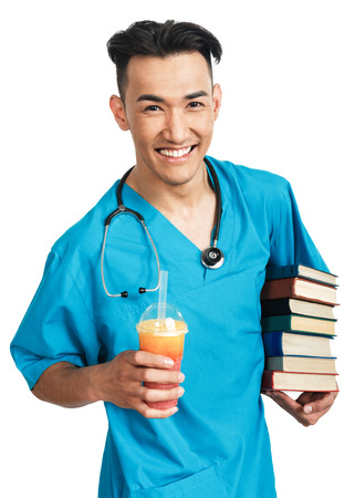 ice cram: a young serious male medical student (nurse, intern, doctor) with a bunch of books and slush ice cram Stock Photo