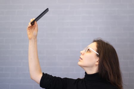 Young woman lifted the phone up to search for communications and the Internet. Banco de Imagens