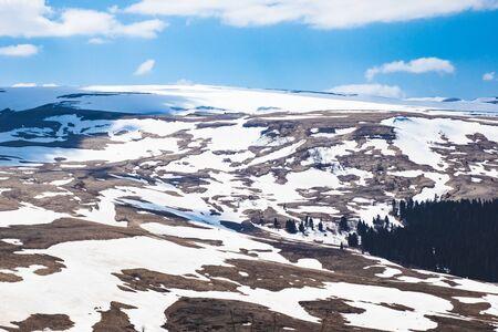 Lago Naki spring plateau with snowy hills, blue sky and clouds. Stok Fotoğraf