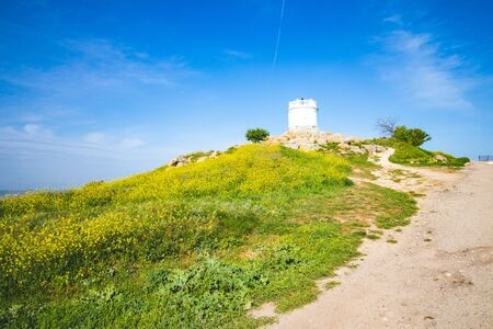 White tower on the top of the hill, to which the road leads Stock Photo