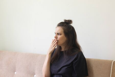 Sick young woman sits at home with a sore throat and coughs