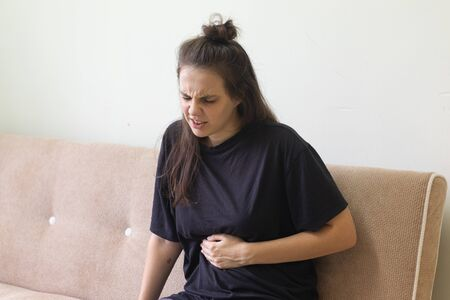 Young woman suffering from stomachache sitting at home on the sofa.