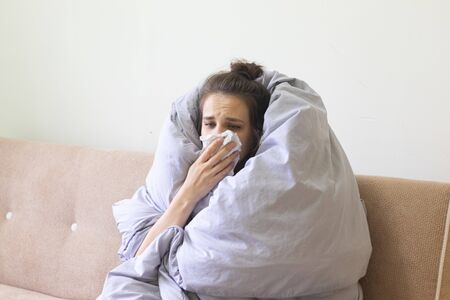 Sick young woman in blanket sits at home with a runny nose