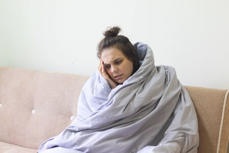 Sick young woman in blanket sits at home with severe headache.
