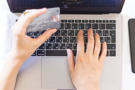 Woman pays for purchases over the Internet with a credit card 写真素材