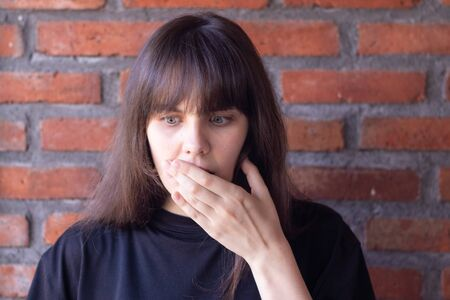 Young brunette woman with bangs wearing a black t-shirt shock by an unpleasant surprise on brick wall background