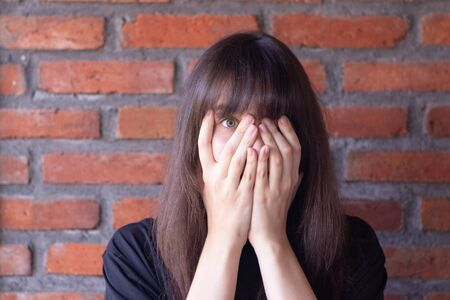 The young brunette woman with bangs wearing a black t-shirt is greatly scared and she covers her face in fear on brick wall background