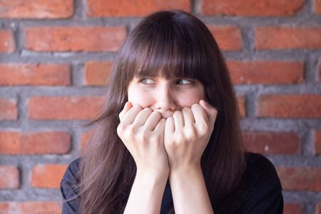 The young woman is greatly scared and she covers her face in fearThe young brunette woman with bangs wearing a black t-shirt is greatly scared and she covers her face in fear on brick wall background 写真素材