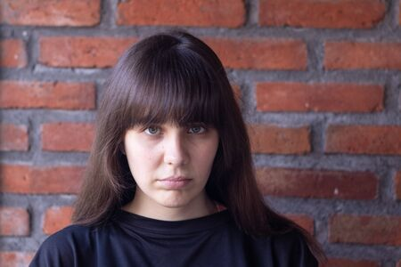 Young very upset brunette woman with bangs wearing a black t-shirt ashamed on brick wall background