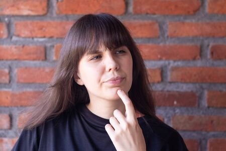Portrait of a beautiful young pensive brunette woman with bangs wearing a black t-shirt on brick wall background 写真素材