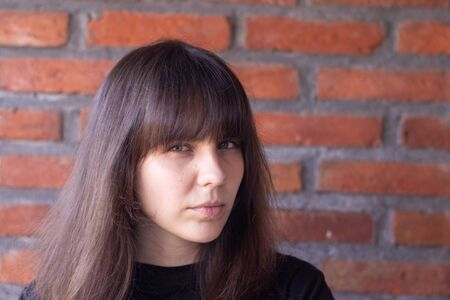 Portrait of a sad brunette woman with bangs wearing a black t-shirt on brick wall background