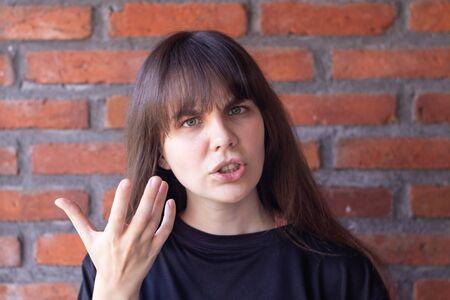 紛争のために叫ぶ黒いTシャツを着た前髪を持つ迷惑なブルネットの女性は、レンガの壁の背景にすべての怒りと怒りを示しています