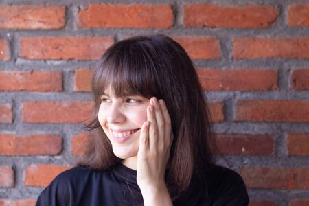 Portrait of a beautiful brunette woman with bangs wearing a black t-shirt who is happy and smiling on brick wall background