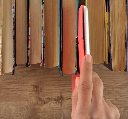 science education: Hand taking tablet from bookshelf