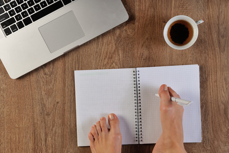 person writing: disable person writing with foot in notebook infront of laptop
