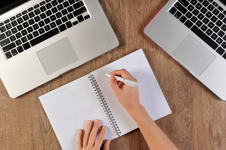 person writing: person writing in notebook infront of two laptops Stock Photo