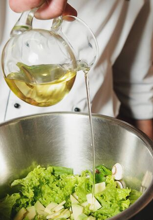 young add: chef adding oil in vegetarian salad