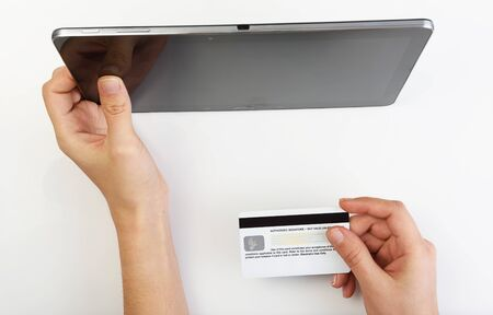 via: Buying with credit card via tablet on white background Stock Photo