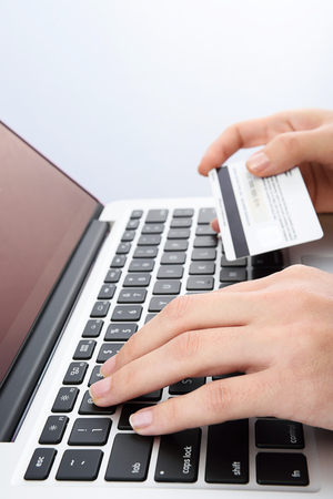 hand card: Vertical picture of Human next to laptop with credit card on white background Stock Photo