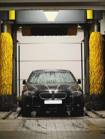auto glass: Black car washing in station washing tunnel