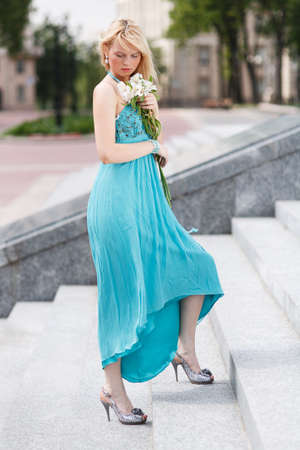 look down: Blond Girl on stairs with flower on hand look down Stock Photo