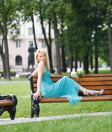 summer dress: blond girl sitting on bench summer dress Stock Photo