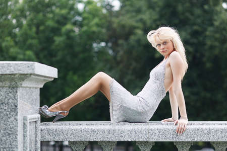 long feet: Blond hair girl in silver dress with long feet Stock Photo