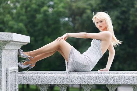long feet: Blond model girl in silver dress in summer with long feet