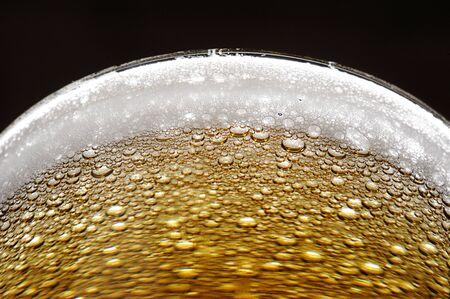 cerca de las burbujas en la espuma de la cerveza en vidrio Foto de archivo